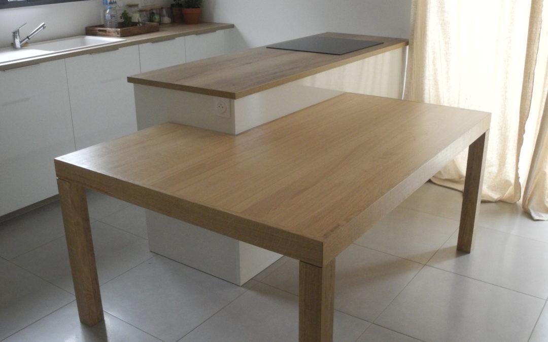Une table de salle à manger autour d'un ilot de cuisine